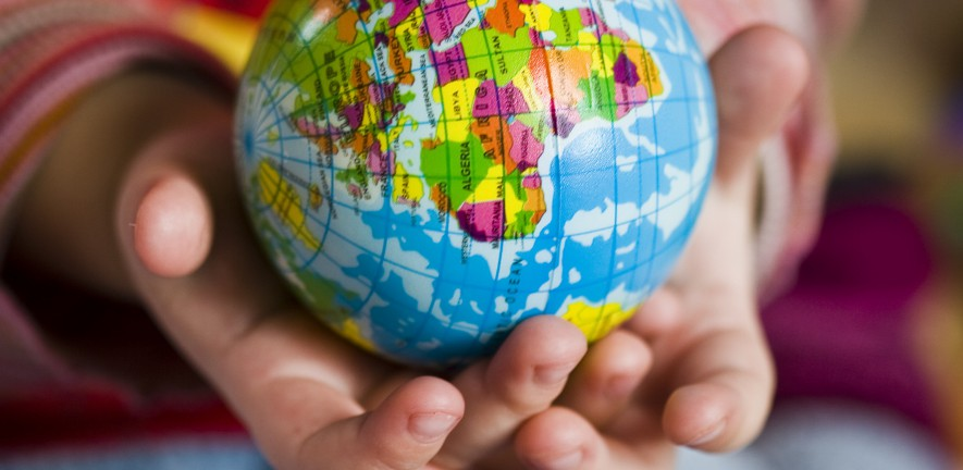 Photo of a pair of hands holding a small world globe, showing the African subcontinent